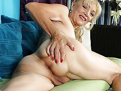 Dissolute aged damsel taking off her bra